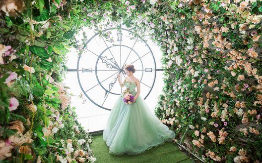 Обои Девушка азиатка в пышном платье с букетом в руке стоит возле больших часов в беседке