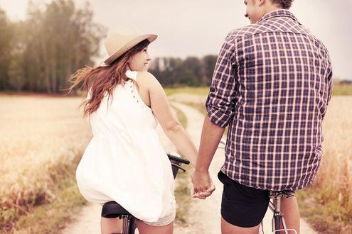 Обои Парень в клетчатой рубашке и девушка в белом платье и шляпке едут на велосипедах, держась за руки и друг другу улыбаясь