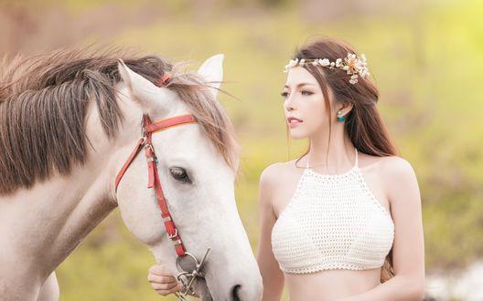 Обои Девушка в белом топике и с венком на голове стоит возле лошади