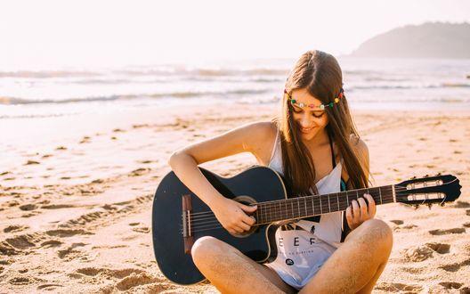 Обои Девушка с гитарой в руках сидит на песке у моря