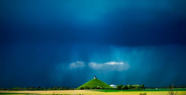 Обои Зеленый холм с памятником на вершине на фоне дождевого неба, Бельгия / Belgium