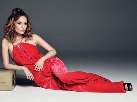Обои Актриса Michael Schwart позирует в красном комбинезоне, сидя на сером фоне