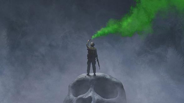 Обои Главный герой фильма Конг: Остров черепа / Kong: Skull Island капитан Джеймс Конрад стоит на огромном черепе и держит в руке дымовую шашку с зеленым дымом