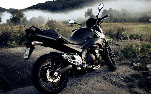 Обои Черный мотоцикл на фоне туманных гор