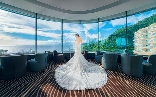 Обои Девушка в белом, длинном платье стоит в одной из комнат гостиницы у окна с видом на море