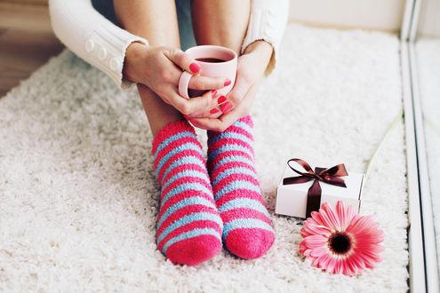 Обои Девушка в ярких носочках с чашкой в руках, около нее лежит подарок и цветок герберы