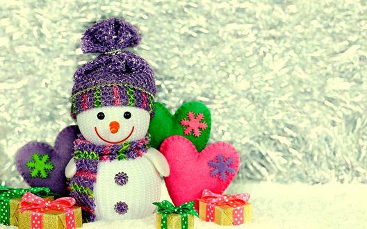 Обои Вязаный Снеговик рядом с подарками и сердечками на фоне серебристой мишуры