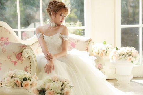 Обои Рыжеволосая азиатка в свадебном платье сидит на диване, рядом вазы с розами