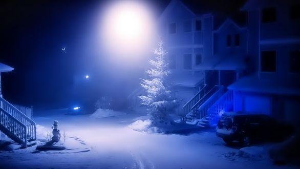 Обои Ночью на улице стоит снеговик и на него падает свет