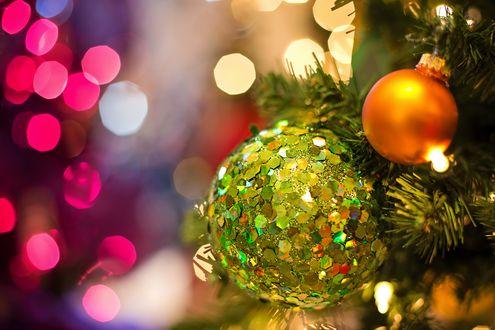 Зеленый и золотой шары висят на елке на размытом фоне