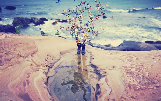 Обои На крутом берегу моря в луже отражается силуэт девочки, с ботинок которой взлетает стайка разноцветных бабочек