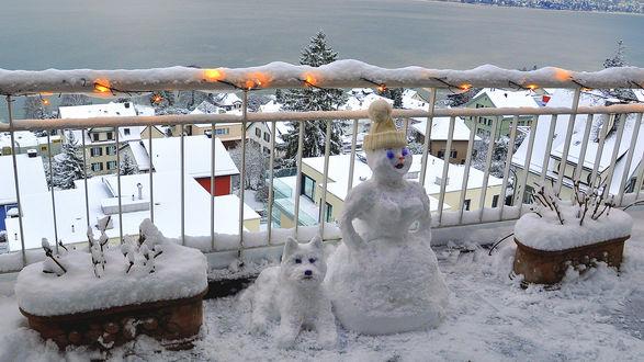 Обои Два снеговика, снежная баба и снежная собачка, стоят возле ограды с гирляндой, на фоне зимнего города