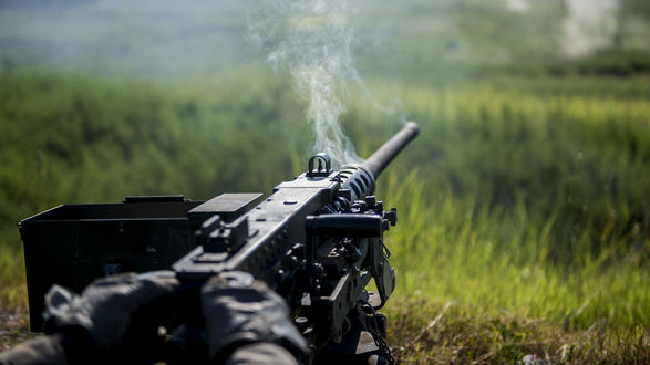 Обои Дымящийся пулемет на поле боя