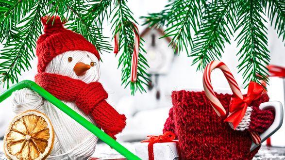 Обои Кружка и снеговик стоят под веточками ели