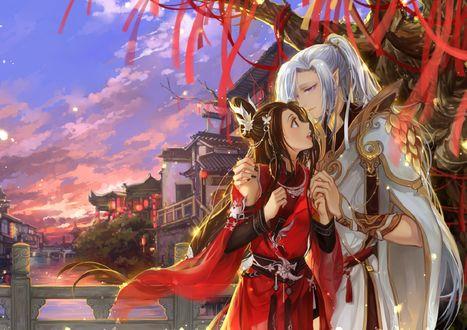 Обои Парень с девушкой обнимаются под священным деревом с красными ленточками