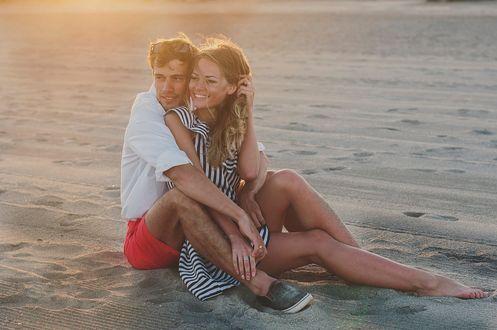 Обои Милая влюбленная пара сидит на песке, фотограф Oxana Denezhkina