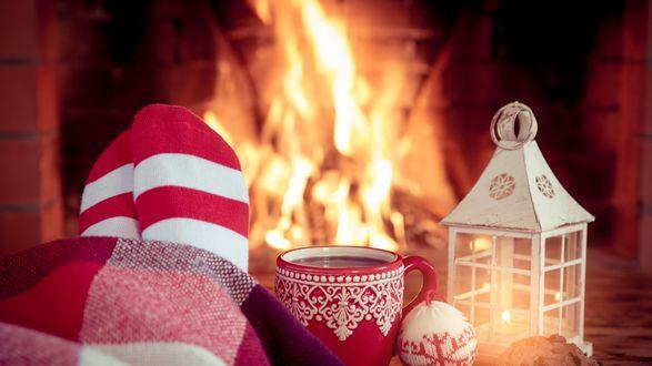 Обои Ножки в полосатых носках, укутанные клетчатым пледом, чашка чая и фонарь на столе у камина