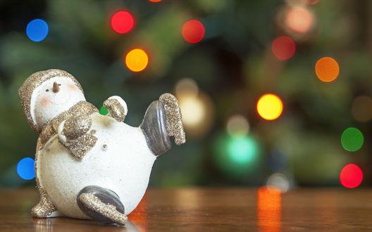 Обои Игрушечный снеговик в коньках на размытом фоне