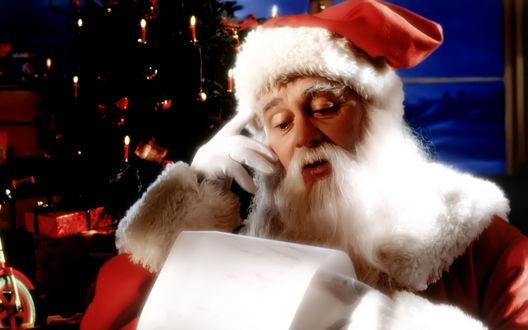 Обои Санта Клаус читает письмо возле елки