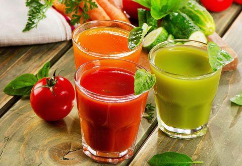 Обои Три стакана свежевыжатого сока помидора, моркови и огурца стоят на деревянном столе