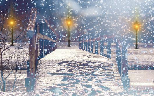 Обои Следы на снегу на деревянном мостике с горящими фонарями на берегу