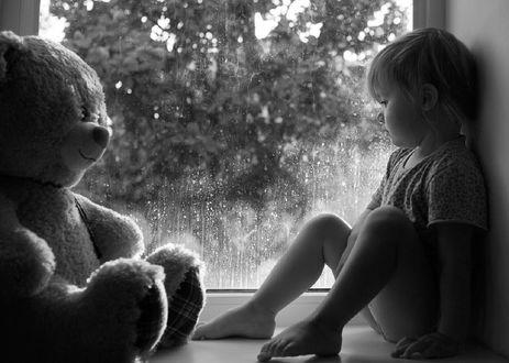Обои Ребенок сидит напротив игрушечного мишки на подоконнике окна, за которым идет дождь, фотограф Коротун Юрий
