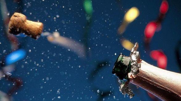 Обои На фоне праздничных лент летит пробка от шампанского