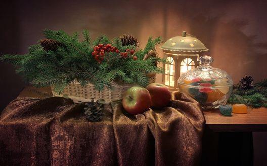 Обои Вазочка с мармеладом стоит на столе возле фонарика и корзинки с хвойными веточками, рядом лежит два яблока