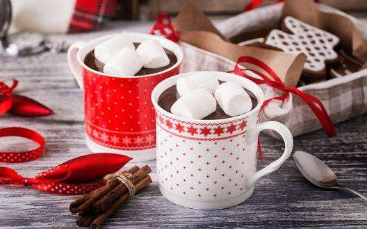 Обои Две кружки горячего шоколада с маршмеллоу стоят на деревянном столе возле коробочки с печеньем, рядом лежат палочки корицы и ленточки