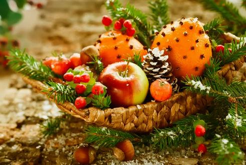 Обои Фрукты, лесные орехи и ягоды лежат в плетеном кузовке, украшенном еловыми веточками и шишками