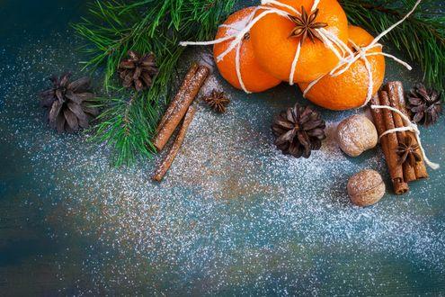 Обои Мандарины, палочки корицы, орехи и шишки с веточками ели на голубой поверхности