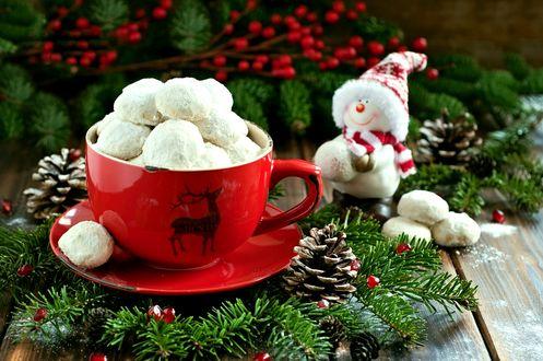 Обои Печенье в сахарной пудре в чашке среди еловых веток с ягодами и шишками, рядом стоит милый снеговик
