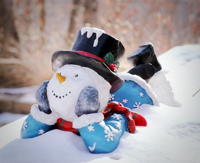 Обои Снеговик лежит на снегу