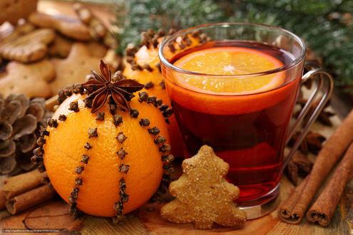 Обои На столе кружка чая с долькой апельсина, апельсин, украшенный корицей и гвоздикой, печенье, ветка елки, шишка и палочки корицы