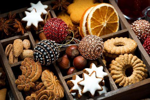 Обои Коробка с новогодними сладостями-печеньем, орехами, каштанами, корицей, дольками апельсина, и елочные шарики