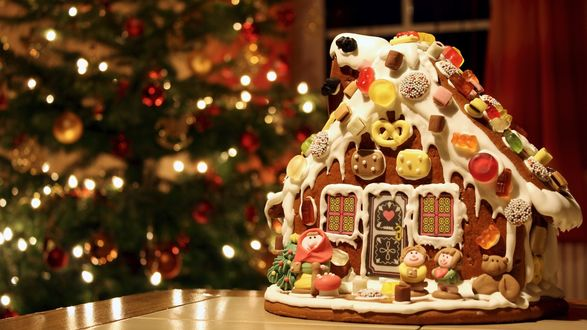 Обои Домик-пряник украшенный фигурками гнома, медведя, печеньем, стоит на столе на фоне новогодней елки