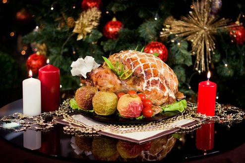 Обои На столе в тарелке рыба, запеченная с яблоками, свечи на фоне новогодней елки