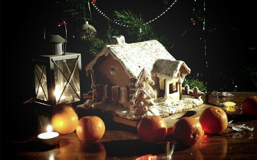 Обои На столе стоит домик-пряник с елкой, рядом яблоки, светит фонарик, на фоне новогодней елки