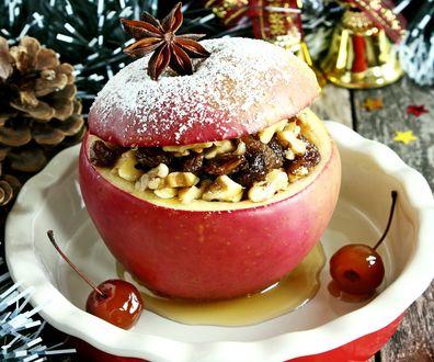 Обои Яблоко с начинкой из орехов и ягод варенья на фоне игрушек и шишки