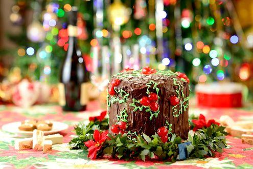 Обои Рождественский торт с шоколадным кремом и ягодами в центре венка из пуансетии с листьями, вокруг сладости, на размытом фоне новогодней елки