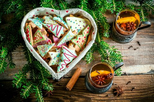 Обои Фигурное разноцветное печенье в корзинке среди еловых веток и чая с лимоном и специями