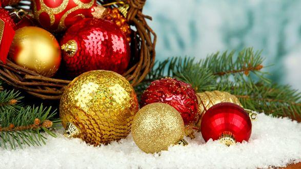 Обои Золотые и красные елочные игрушки в корзинке и на снежной крошке с еловыми ветками