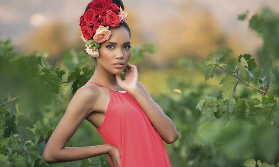 Обои Смуглая девушка с красными и белыми розами в волосах стоит на фоне виноградных листьев, фото Nicole Cook / Николь Кук