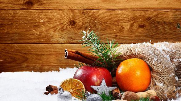 Обои Апельсин, красное яблоко и пряности лежат на снегу с еловыми ветками