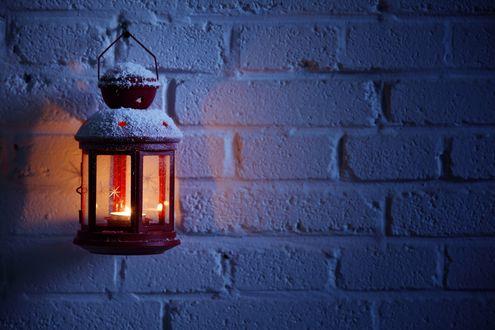 Обои Горящий уличный фонарь на белой кирпичной стене дома запорошен снегом