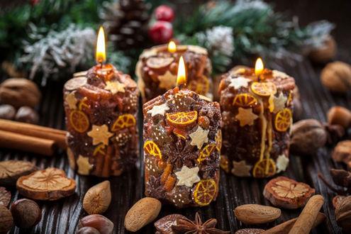 Обои На столе горящие свечи, украшенные фигурным печеньем, лимоном, орехи, сушеные фрукты, ветка елки