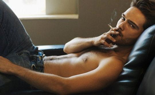 Обои Красивый, молодой мужчина лежит в кресле, курит сигарету на фоне окна