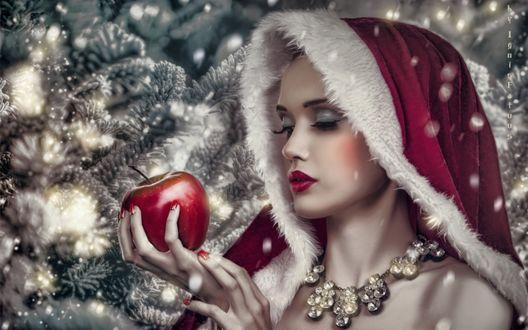 Обои Девушка в новогодней накидке держит в руке яблоко на фоне елок
