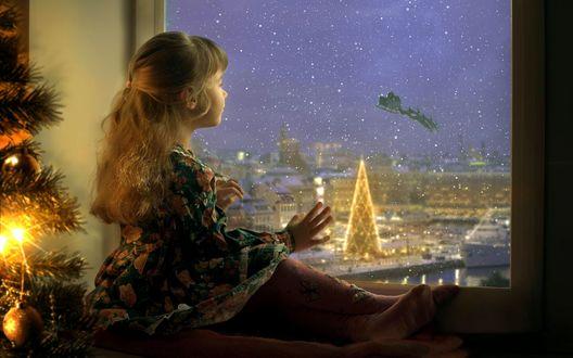 Обои Девочка сидит у окна возле елки и смотрит на вечерний город, по небу пролетает карета Санты с оленями