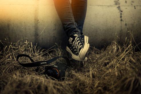 Обои Ножки в кедах и камера в траве